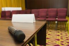 Микрофон на таблице на предпосылке залы или конференц-зала пресс-конференции Стоковая Фотография RF