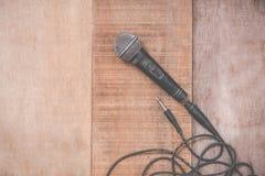 Микрофон Grunge с кабелем на деревянной предпосылке Стоковое фото RF