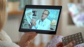микстура он-лайн Молодая женщина советуя с с ее доктором используя видео-чат дома видеоматериал