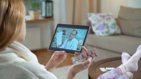 микстура он-лайн Молодая женщина советуя с с ее доктором используя видео-чат дома акции видеоматериалы