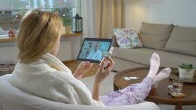 микстура он-лайн Молодая женщина советуя с с ее доктором используя видео-чат дома сток-видео