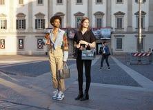 МИЛАН, ИТАЛИЯ - 15-ОЕ ИЮНЯ 2018: 2 модели представляя для фотографов в квадрате Duomo после модного парада АЛЬБЕРТЫ FERRETTI стоковые фото