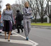 МИЛАН - 25-ОЕ ФЕВРАЛЯ 2018: Модные женщины идя для фотографов в улице перед модным парадом ARMANI Стоковая Фотография RF