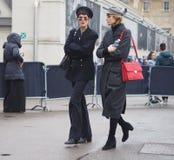 МИЛАН - 22-ОЕ ФЕВРАЛЯ 2018: 2 модных женщины идя в улицу после модного парада LES COPINS, во время недели моды милана Стоковое Изображение