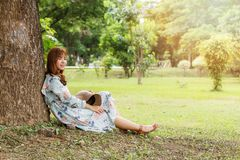 Милая азиатская девушка в полагаться винтажного платья сидя против на дерева ослабляя Винтажный тон стоковые изображения