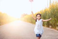 Милая азиатская девушка маленького ребенка играя с ветротурбиной Стоковые Фото