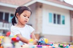 Милая азиатская девушка маленького ребенка играя с красочными блоками игрушки Стоковая Фотография RF