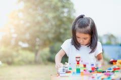 Милая азиатская девушка маленького ребенка играя с красочными блоками игрушки Стоковые Изображения RF