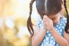 Милая азиатская девушка маленького ребенка моля с сложенный ее руке Стоковое Изображение