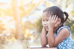 Милая азиатская девушка маленького ребенка отдыхает ее подбородок на ее руках Стоковое фото RF
