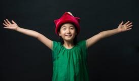 Милая азиатская девушка одела в зеленом платье с fairy шляпой и 2 оружия широко раскрывают на черной предпосылке стоковые фото