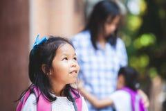 Милая азиатская девушка ребенка ждать ее сестру для того чтобы пойти обучить совместно после объятия их мать стоковые фотографии rf