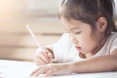 Милая азиатская девушка ребенка имея потеху, который нужно нарисовать и покрасить с crayon Стоковая Фотография RF