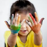 Милая азиатская девушка ребенка при руки покрашенные в красочной краске Стоковое фото RF