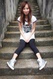 Милая азиатская девушка сидя вниз на шагах стоковое изображение rf