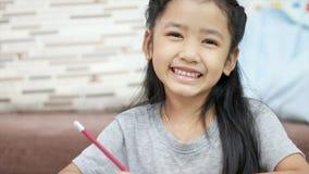 Милая азиатская маленькая девочка усмехаясь с счастьем с составом космоса экземпляра видеоматериал