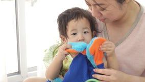 Милая азиатская мать с меньшим ребенком играя совместно в живущей комнате, сток-видео