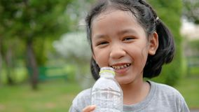 Милая азиатская питьевая вода маленькой девочки с счастьем на общественном парке природы акции видеоматериалы