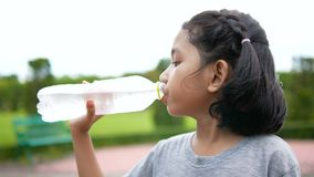 Милая азиатская питьевая вода маленькой девочки с счастьем на общественном парке природы сток-видео