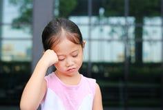 Милая азиатская позиция девушки ребенка ее рука на голове с меньшей улыбкой стоковая фотография rf