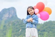 милая азиатская улыбка девушки и воздушный шар держать, стоковое фото