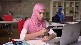 Милая арабская девушка в розовом hijab печатает с на пальцем ее холодок телефона пока сидящ на ее рабочем месте, коллегах дальше сток-видео