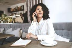Милая Афро-американская девушка сидя в ресторане и говоря на ее даме мобильного телефона молодой в белой рубашке сидя внутри Стоковое Изображение