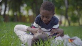 Милая Афро-американская женщина лежа на траве в зеленом парке, ее маленький сын лежа поверх ее Мать и мальчик акции видеоматериалы