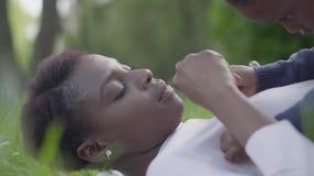 Милая Афро-американская женщина лежа на траве в парке, ее маленький сын лежа поверх ее Мать и мальчик видеоматериал