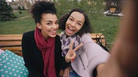 Милая Афро-американская женщина 2 принимая selfie на smartphone с хозяйственными сумками и усмехаться Подруги сидя дальше Стоковое Фото
