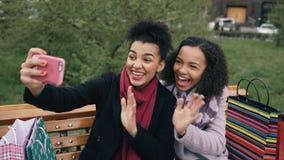 Милая Афро-американская женщина 2 принимая selfie на smartphone с хозяйственными сумками и усмехаться Подруги сидя дальше Стоковые Изображения