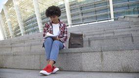 Милая афро-американская студентка делая домашнюю работу outdoors, усмехающся в камеру видеоматериал