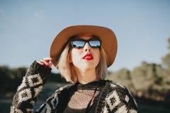 Милая белая женщина с шляпой и солнечными очками наслаждаясь outdoors и смотря голубое небо Стоковые Изображения RF