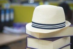 Милая белая соломенная шляпа положенная на книгу стоковое фото rf
