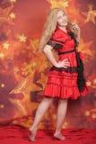 милая белокурая девушка в красном положении платья сказки на оранжевой предпосылке со звездами стоковые фото