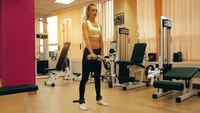 Милая белокурая девушка практикуя в спортзале с гантелями