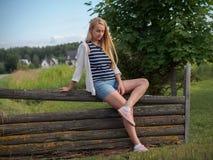 Милая белокурая женщина представляя на старое деревянном обнести шорты джинсовой ткани Стоковая Фотография