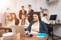 Милая беременная женщина говоря на шлемофоне в офисе Беременная коммерсантка в офисе стоковая фотография rf