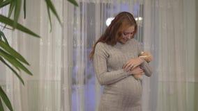 Милая беременная женщина с длинной лаской волос золота ее живот прижимаясь мягкая игрушка акции видеоматериалы