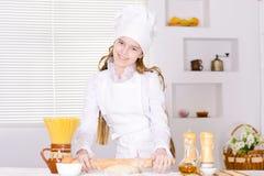 Милая выпечка девушки в кухне Стоковое Фото