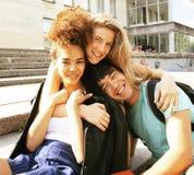 Милая группа в составе teenages на здании университета с книгами Стоковое Изображение