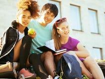 Милая группа в составе teenages на здании университета с книгами Стоковые Фото