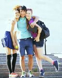 Милая группа в составе teenages на здании университета с книгами Стоковые Изображения