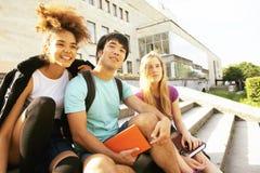 Милая группа в составе teenages на здании университета с huggings книг, назад к школе Стоковые Фото