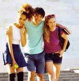 Милая группа в составе teenages на здании университета с huggings книг, назад к школе Стоковые Фотографии RF