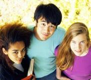 Милая группа в составе teenages на здании университета с huggings книг, нациями разнообразия Стоковое Изображение RF
