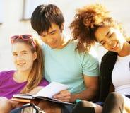 Милая группа в составе teenages на здании университета с huggings книг Стоковые Фото