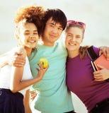 Милая группа в составе teenages на здании университета с huggings книг Стоковое Изображение RF