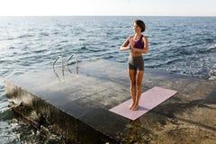 Милая дама в sporty верхней части и шорты делая йогу с видом на море на предпосылке стоковое изображение