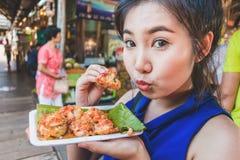 Милая девушка азиатское счастливого для еды мини зажаренных мидий в плавать m стоковое фото